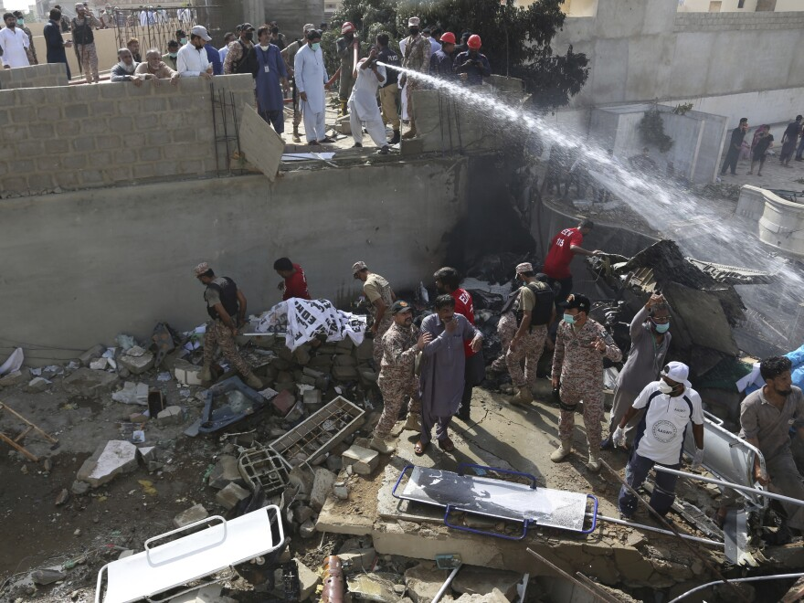 Soldiers and volunteers search the wreckage at the site of the Pakistan International Airlines crash in Karachi, Pakistan, on Friday.
