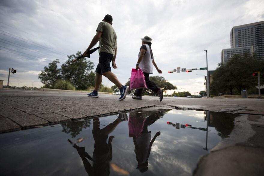 Pedestrians walk along Cesar Chavez.
