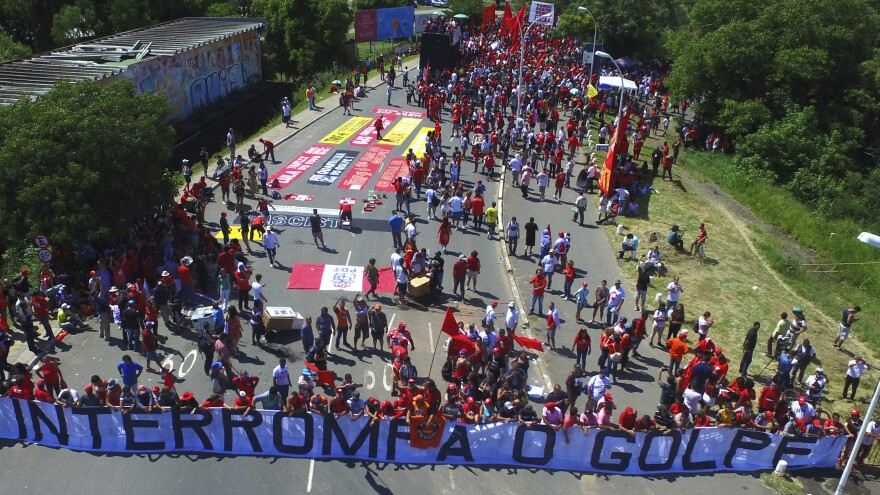 """Lula's supporters hold a banner that reads, in Portuguese, """"Stop the Coup."""" The demonstrators had gathered Wednesday near the court in Porto Alegre, Brazil, where judges ruled unanimously to uphold the former president's graft conviction."""