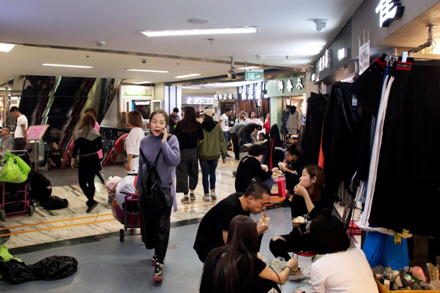 Merchants eat lunch in their stalls at Beijing's largest wholesale clothing market. Merchants complain that the government wants them to move out of Beijing, but has offered them no compensation