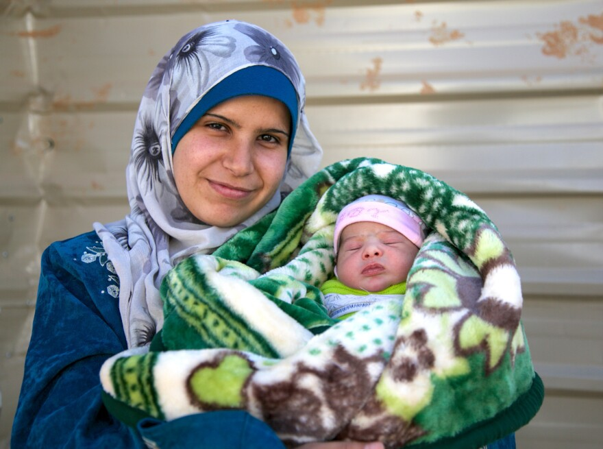 Khoulod, 21, holds Rima, her second child — the 5000th baby registered in Jordan's Zaatari Refugee Camp.