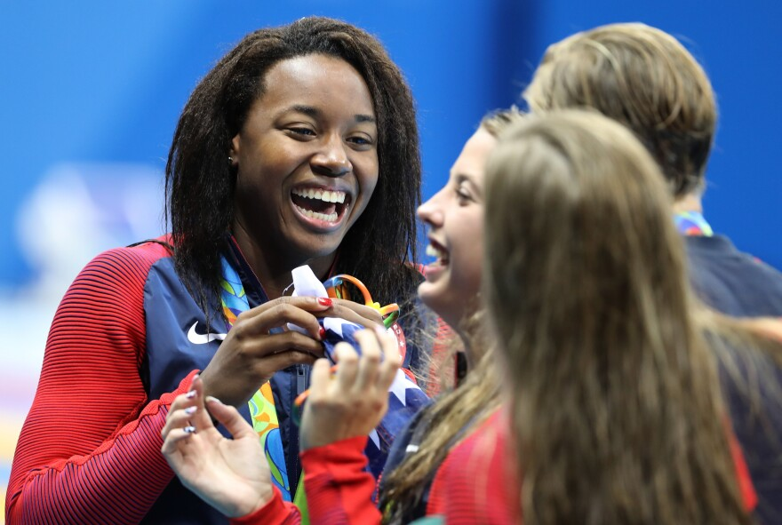 Simone Manuel (left) celebrates with U.S. teammates Kathleen Baker, Lilly King and Dana Vollmer during the medal ceremony for the Women's 4 x 100m Medley Relay Final on Saturday.