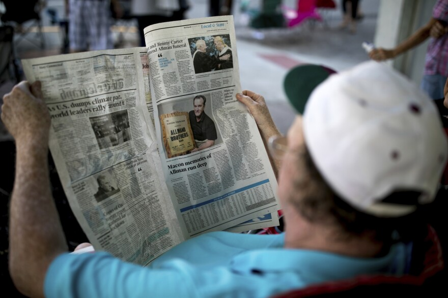 Dwayne Lewis reads a local newspaper covering the death of Gregg Allman, Saturday, June 3, 2017, in Macon, Ga. (Branden Camp/AP)