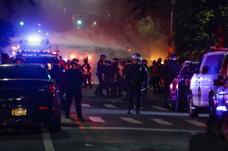 Firefighters spray water on a burning police car after protesters rallied at the Barclays Center on May 29 in the Brooklyn borough of New York.