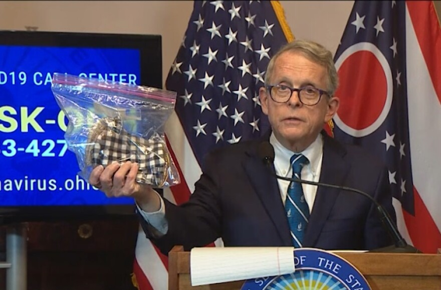 Gov. Mike DeWine holds up a baggie with homemade masks at a press conference in April. He encouraged people to start wearing masks then, but they weren't required until a statewide order in July.