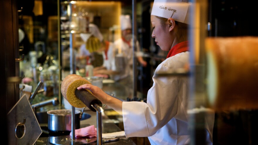 A chef prepares the <em>baumkuchen</em>, a German layer cake made on a stick that when cut, resembles a tree with concentric rings.