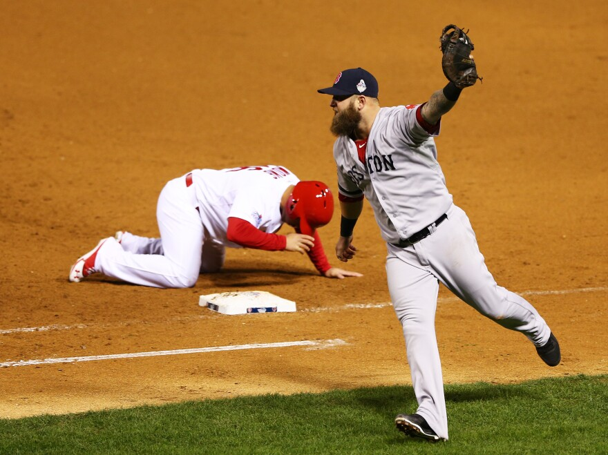 Kolten Wong of the St. Louis Cardinals slumps as Boston Red Sox first baseman Mike Napoli celebrates Sunday night. Wong was picked off at first base to end the game and the Cardinals' hopes of winning. Boston's 4-2 victory means the World Series is tied at 2-2.