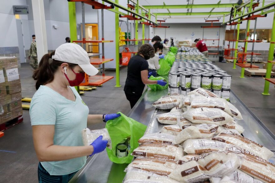 Volunteers packs food into bags in an assembly line at the Houston Food Bank warehouse.