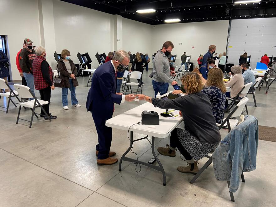 Gov. Mike DeWine checks in to vote at the Cedarland Event Center in Cedarville, after waiting in line to vote on Election Day.