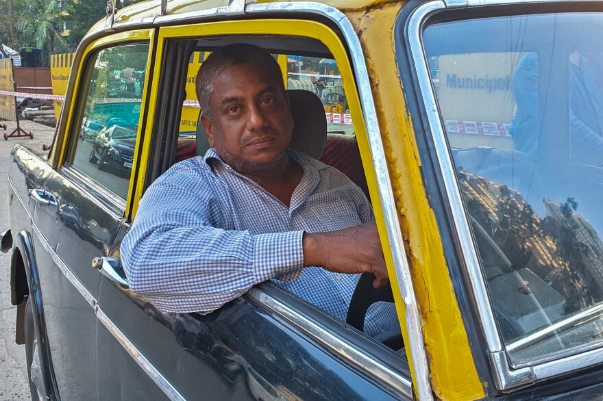 Abdul Kareem sits behind the wheel of his Premier Padmini taxi — which will go off Mumbai's streets by the summer.