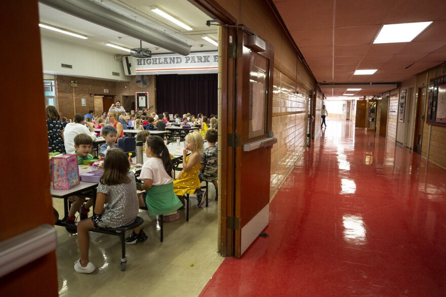 Students eat lunch in the cafeteria of Highland Park Elementary. A sole person walks in an empty hallway.