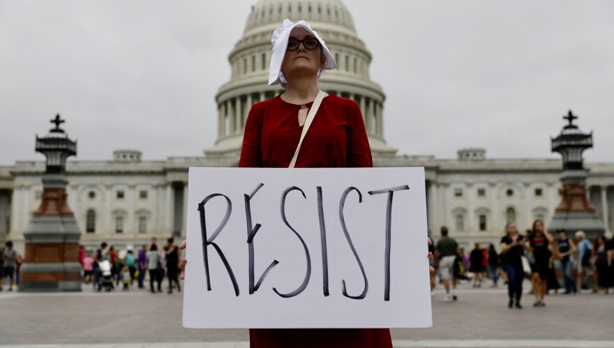 A protester wearing a handmaiden outfit observes a moment of silence for sex abuse survivors during a protest against the nomination of Brett Kavanaugh to the Supreme Court.