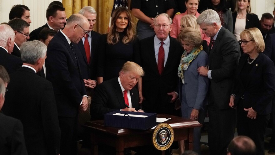Flanked by lawmakers and first lady Melania Trump, President Trump participates in a bill signing to dedicate more resources to fight the opioid crisis during an East Room event at the White House Wednesday.
