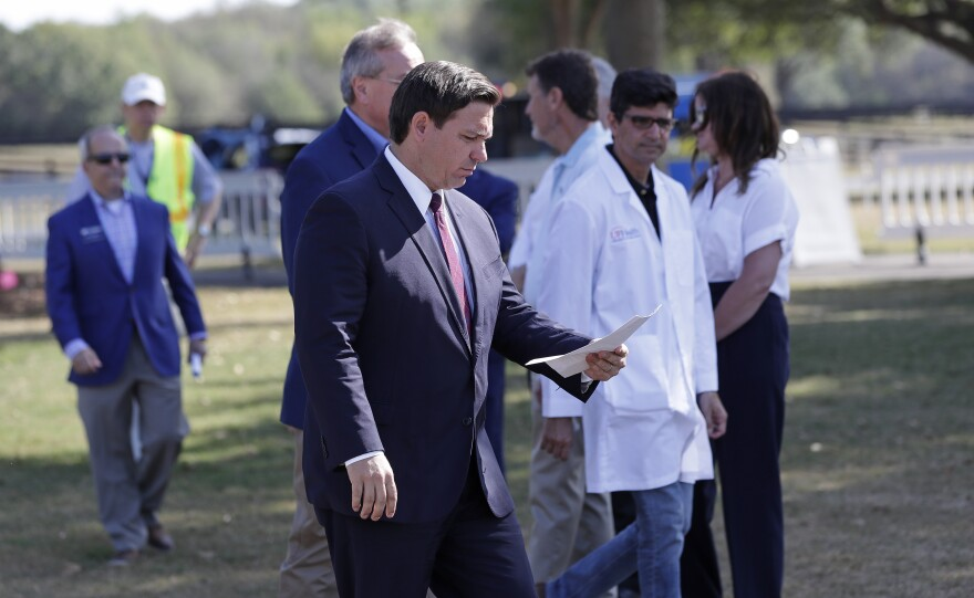 In this March 23, 2020 file photo, Florida Gov. Ron DeSantis, center front, arrives at a mobile testing site for a press conference Monday, March 23, 2020, in The Villages, Fla. The Villages, a retirement community, is one of the largest concentration of seniors in the U.S. Republican Gov. Ron DeSantis has been walking a tightrope for weeks during the coronavirus crisis, trying to protect both Floridians vulnerable to the virus and the cratering economy in a state of 21 million people.