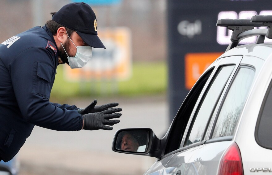 A policeman wearing a face mask warns a driver on the road between Codogno and Casalpusterlengo, which has been closed by the Italian government due to a coronavirus outbreak in northern Italy, February 23, 2020.