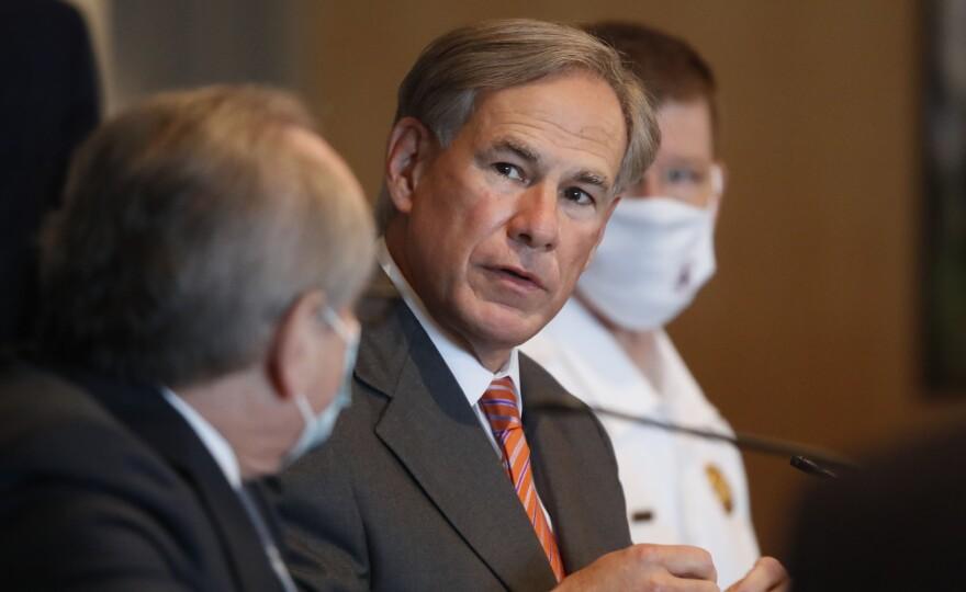 Texas Gov. Greg Abbott, center, speaks to Dr. Daniel Podolskyduring a news conference in Dallas, Thursday, Aug. 6, 2020.