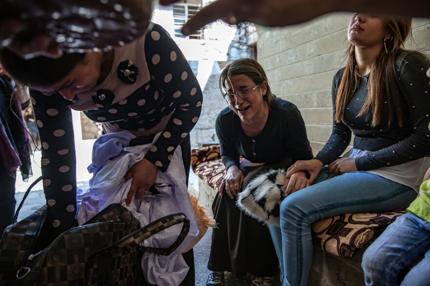 Khairya Murad (right), the sister of Nobel Peace laureate Nadia Murad, and other women from Kocho are overcome with emotion at the Yazidi temple in Lalish. They have brought clothing to be blessed and sprinkled with sacred spring water as part of the burial rites for their family members, once the remains are exhumed from mass graves and identified through DNA tests.
