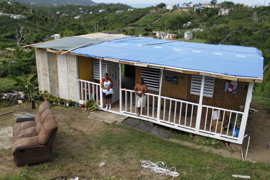 José Ramón Sierra Meléndez and his wife Felicita Garcia stand on their porch of their recently rebuilt house. Meléndez received the tarp and a couple of boxes of water from one passing FEMA truck.