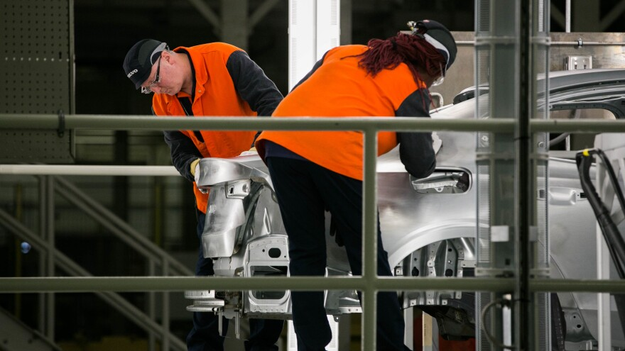 Workers inspect a Volvo S60 sedan's body on June 20, 2018. Robotic sensors examine welds, but human hands and eyes assess the touch and feel of the metal.