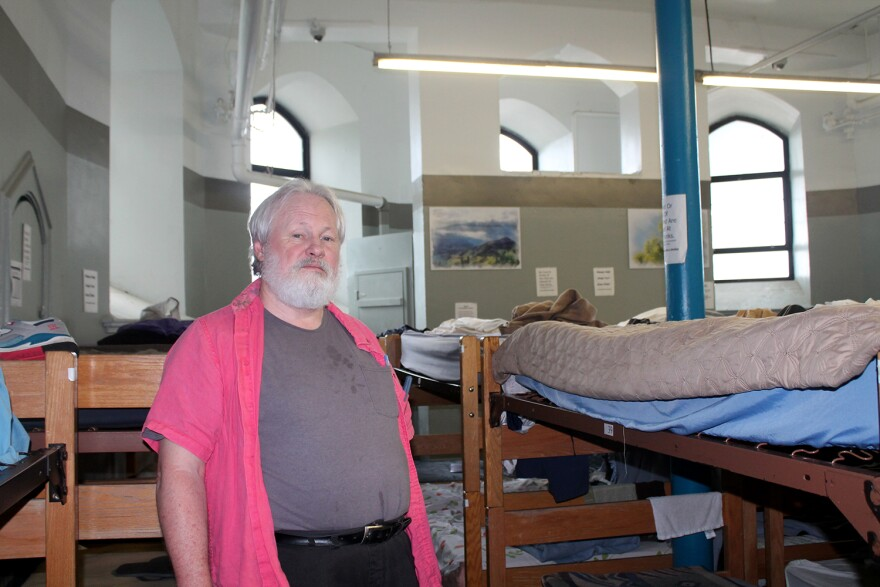 Tom Burnham stands among the bunk beds in the basement of St. Peter and Paul Catholic Church, where Peter and Paul Community Services operates an emergency shelter for men.
