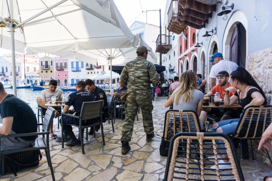 A Greek soldier walks past patrons sipping iced coffee at cafes in Kastellorizo's port.