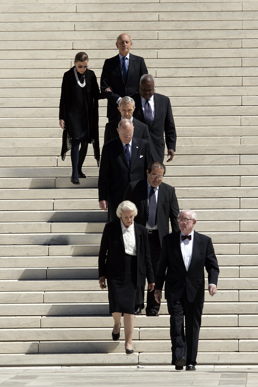 Associate Justices of the Supreme Court, from front to back: John Paul Stevens, Sandra Day O'Connor, Antonin Scalia, Anthony Kennedy, David Souter, Clarence Thomas, Stephen Breyer, and Ruth Bader Ginsburg; walk down the steps of the Supreme Court as they wait for the casket carrying Chief Justice William H. Rehnquist in Sept. 2005.