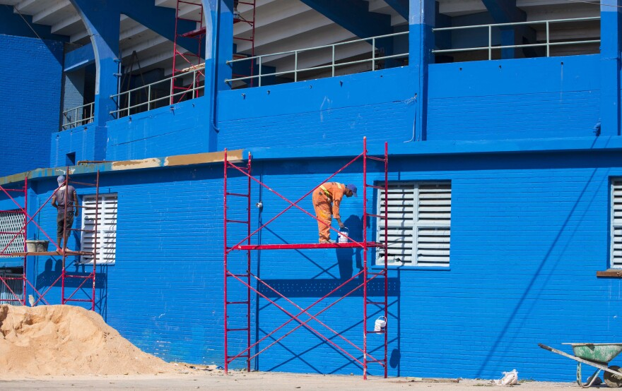 Workers paint the walls outside the Estadio Latinoamericano in Havana, on Tuesday.