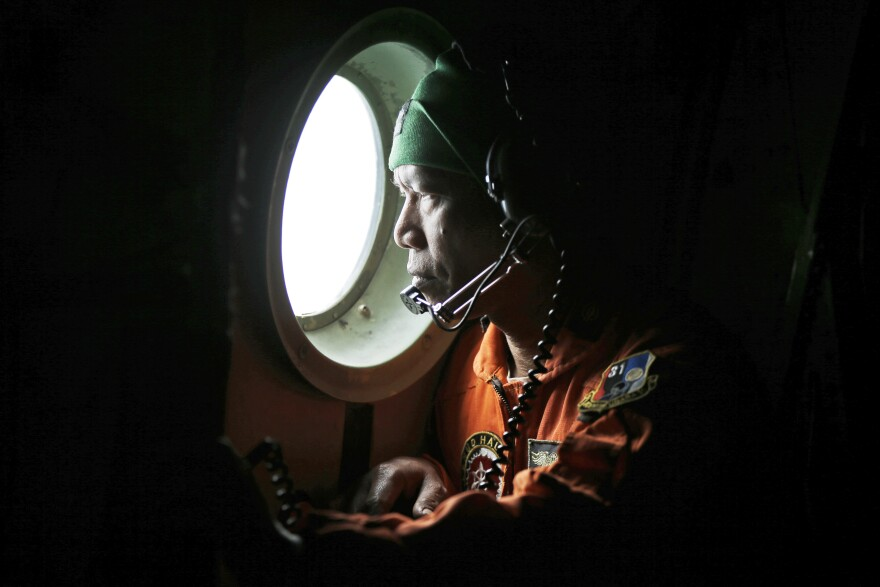 A crew of an Indonesian air force C-130 airplane of the 31st Air Squadron looks out the window during the search for AirAsia Flight 8501 over the waters of Karimata Strait in Indonesia on Monday.