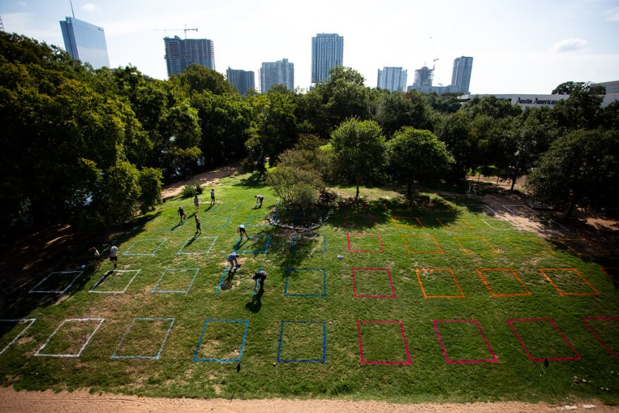 Volunteers with Parkspace spray-paint colorful squares on the grass.