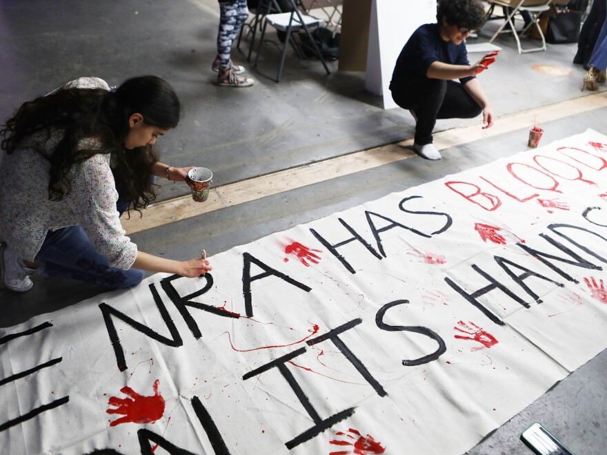 """Young activists paint signs on March 22 to be carried at the """"March For Our Lives"""" in Los Angeles. More than 500,000 are expected to march for gun control at rallies nationwide on March 24."""
