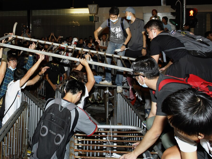 Pro-democracy protesters set up new barricades after riot police retreated from a main road at Mong Kok shopping district in Hong Kong early Saturday.