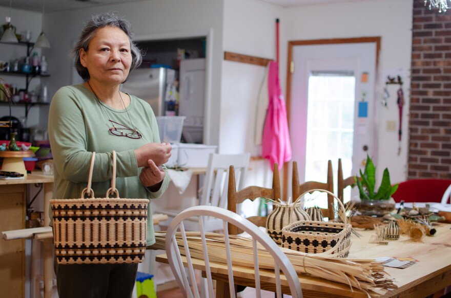 Betty Maney stands by her kitchen table, holding a handle basket.