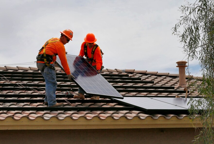 Electricians install solar panels on a roof.