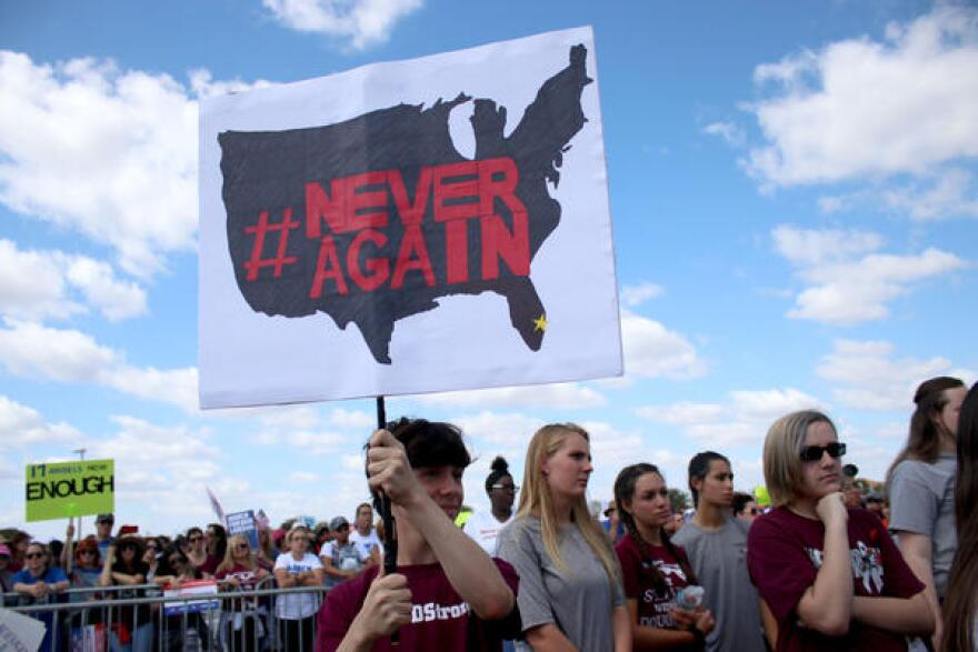 Teens hold aloft a NeverAgain sign before the start of the March For Our Lives event in Parkland Saturday morning.