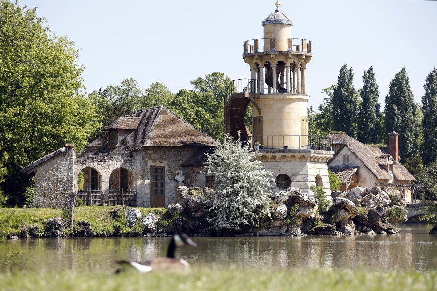 The Marlborough Tower is visible in the garden of <em>Le Hameau de la Reine</em> (The Queen's Hamlet), after it was restored, in Versailles, France. The hamlet was commissioned during the winter of 1782-1783 by Queen Marie Antoinette who wanted to move away from the constraints of the court of Versailles.