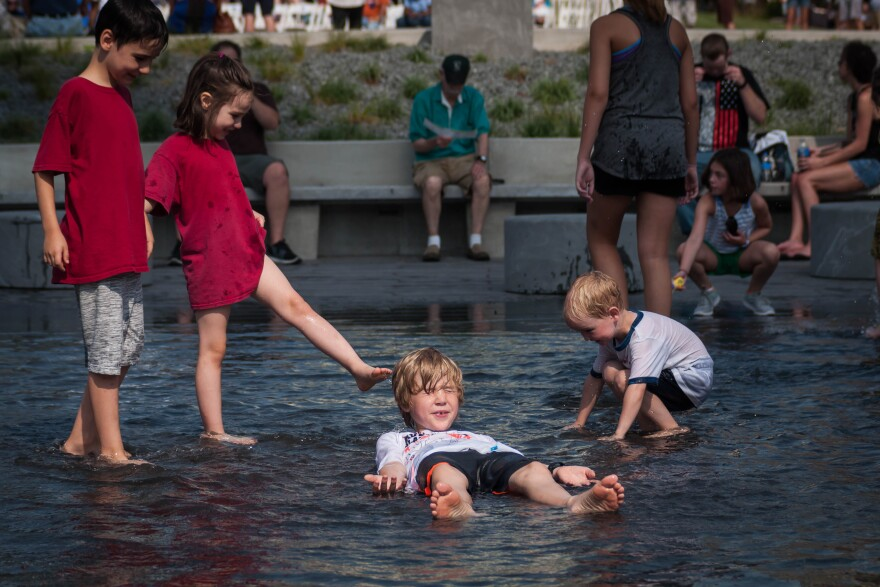 Children play in a fountain in front of the Gateway Arch's new visitor center Tuesday, July 3, 2018, before a ceremony to re-open the park grounds after a multi-year renovation project.