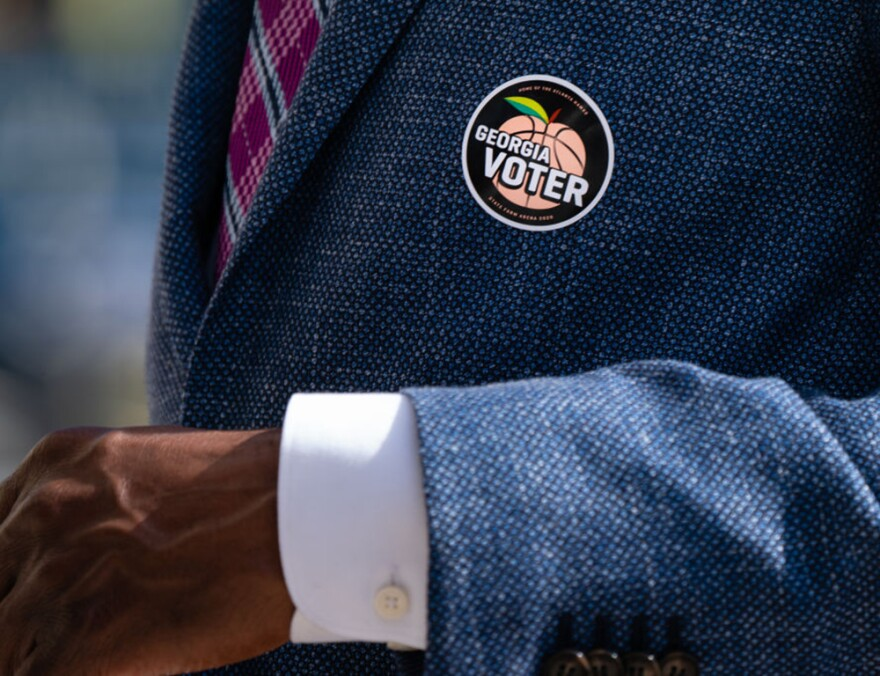 """A """"Georgia Voter"""" sticker is seen on the jacket of Democratic U.S. Senate candidate Raphael Warnock after he cast his ballot during early voting on October 21, 2020 in Atlanta, Georgia. (Elijah Nouvelage/Getty Images)"""