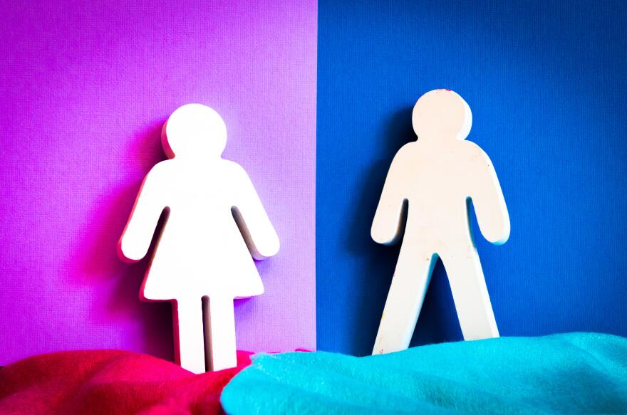 Cutouts of a woman and a man lean against a wall. Behind the woman is a purple color and behind the man is a blue color. The two colors are split down the middle between the space between the man and woman.