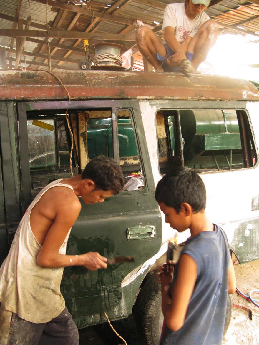 Mechanics at Ohn Myint's car repair shop on the outskirts of Yangon refurbish rusty, decades-old government jeeps.