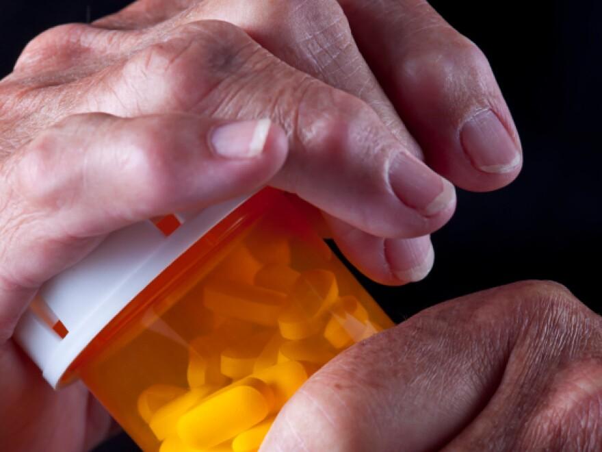 Arthritic senior citizen's hands on a pill bottle.