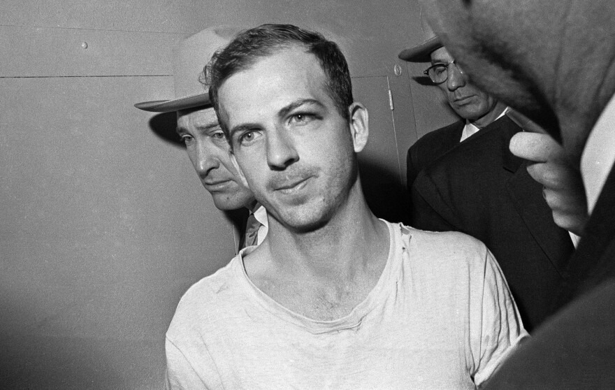 Lee Harvey Oswald is led down a corridor of the Dallas police station for questioning in connection with Kennedy's assassination on Nov. 23, 1963.