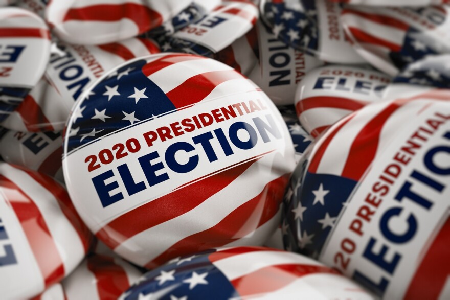 Closeup shot of one presidential election button in focus in between many other buttons in a box.