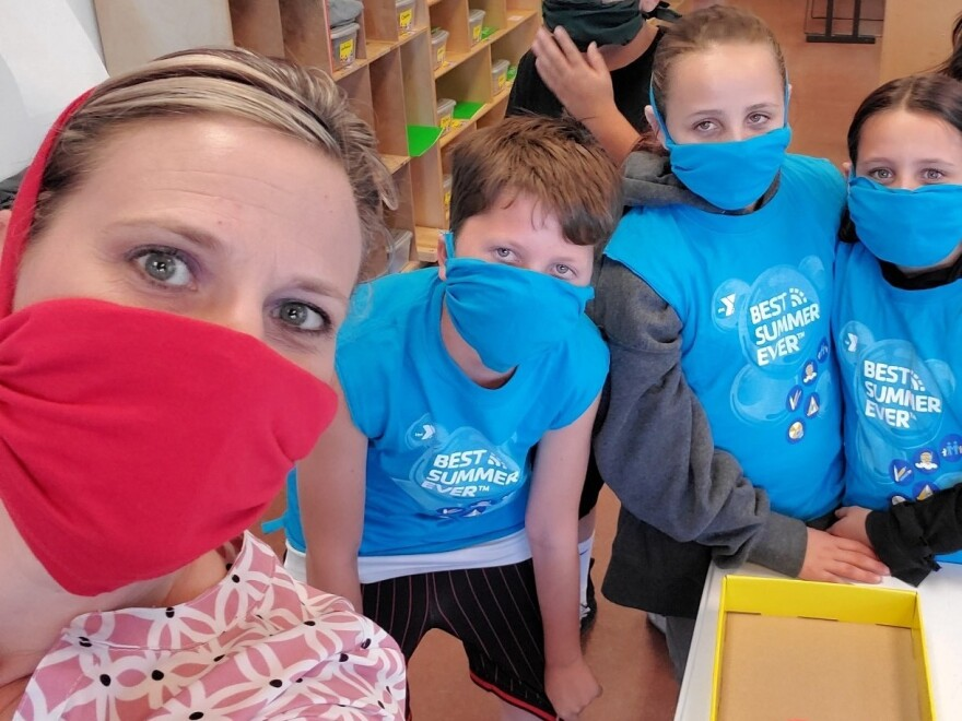 A Valley of the Sun YMCA staff member poses with children after a craft project that involved making face masks.