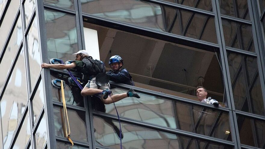 Police grab a man scaling Trump Tower using suction cups Wednesday in New York.