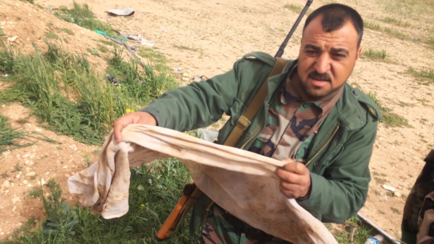 In August, the self-proclaimed Islamic State seized territory near the northern Iraqi village of Hardan. A handful of Yazidis who fled have returned to a grim discovery: mass burial pits. Naif Brahem Khadir holds a traditional man's headdress with blood stains and a bullet hole. It was half-buried in a mound near the village. He believes his uncle and his cousin are among the bodies here.