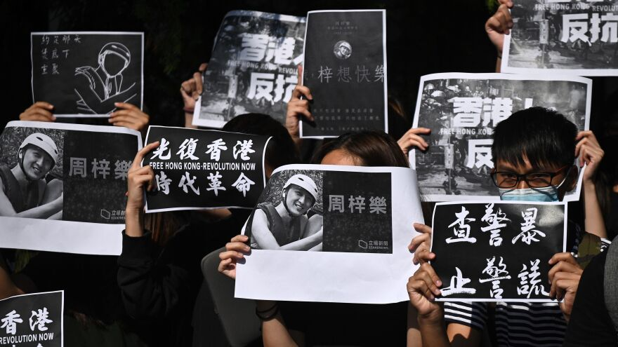 Students of the Hong Kong University of Science and Technology take part in a march toward the school president's lodge Friday, following the death of a student injured during clashes between police and protesters a few days ago.