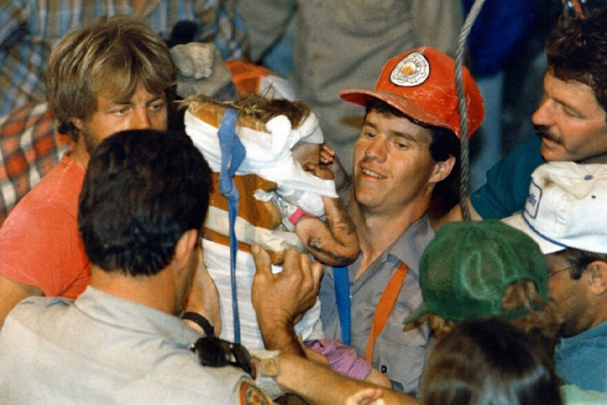 Rescue worker Steven Forbes carries 18-month-old Jessica McClure on Oct. 16, 1987, shortly after she was rescued from an abandoned water well in Midland, Texas.