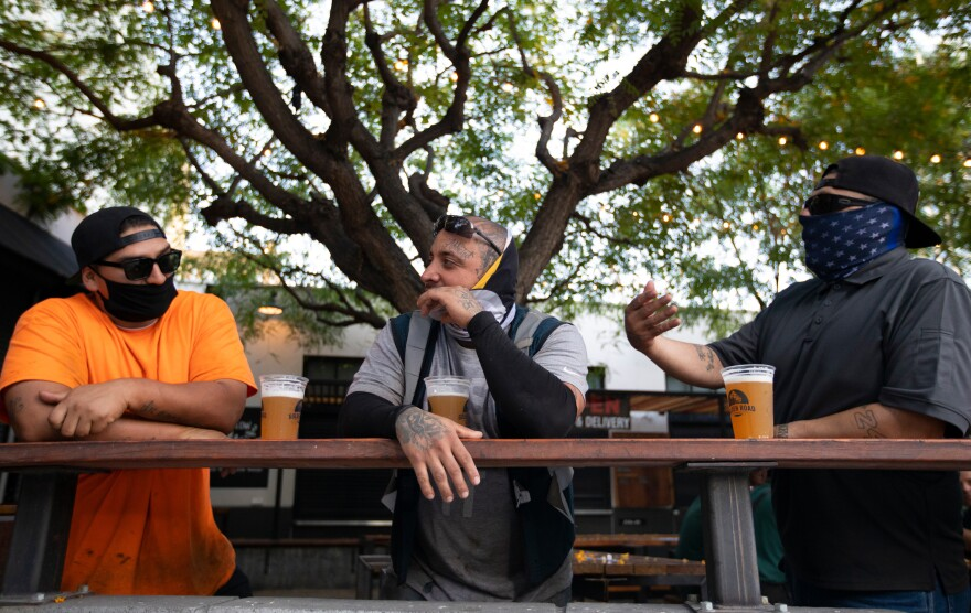 With new coronavirus infections climbing in most states, infectious disease experts are discouraging group get-togethers, especially those that involve drinking. In this photo patrons enjoy a beer outside the Central Market in Los Angeles, this week.
