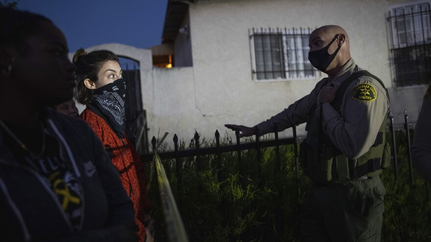 A protester talks with a deputy of the Los Angeles Sheriff's Department during demonstrations following the death of a Black man identified as Dijon Kizzee on Monday in Los Angeles.