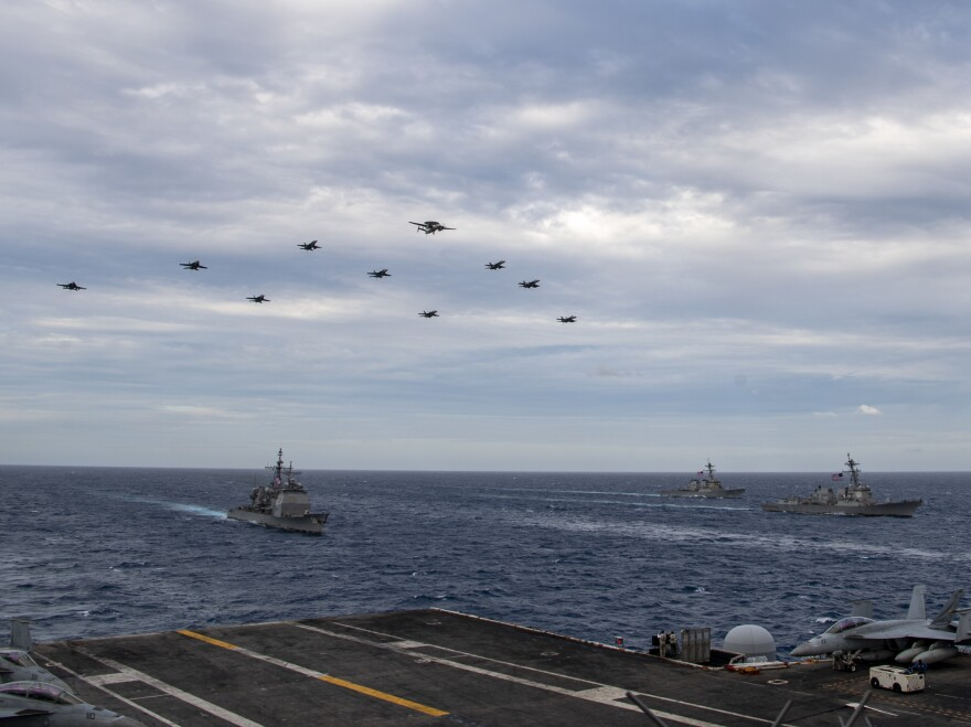 Aircraft assigned to Carrier Air Wing (CVW) 17 fly over the Theodore Roosevelt Carrier Strike Group and the Nimitz Carrier Strike Group in the South China Sea on Tuesday.